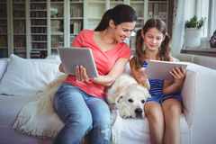 Mother and daughter sitting with pet dog and using digital Royalty Free Stock Photos