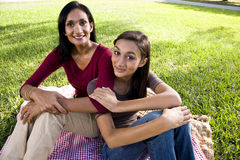 Mother and daughter sitting on picnic blanket Stock Images