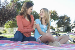 Mother And Daughter Sitting On Picnic Blanket. Low angle view of a smiling mother and daughter sitting on picnic blanket Royalty Free Stock Photo