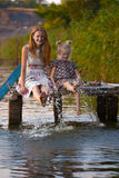 Mother and daughter sitting on the pier. Smiling mother and daughter sitting on the pier warm autumn day dangling his legs in the water and splash in the stock images