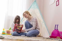 Summation with abacus. Mother and daughter sitting in the playroom, learning summation with abacus. Focus on the mother stock photo