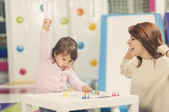 Playing a ludo game. Mother and daughter sitting in a playroom, playing a ludo game; daughter happy because she won the game. Focus on the daughter Stock Photography