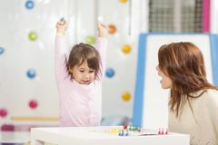 Playing a ludo game. Mother and daughter sitting in a playroom, playing a ludo game; daughter happy because she won the game Stock Photos