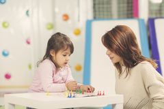 Ludo board game playing. Mother and daughter sitting in a playroom, playing a ludo game and enjoying their time together stock photo