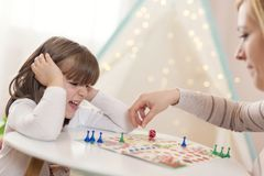Playing a ludo game. Mother and daughter sitting in a playroom, playing a ludo game; mother repositioning the pawn royalty free stock photos