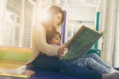 Reading a fairy tale. Mother and daughter sitting in a playroom, reading a fairy tale; daughter sitting in mother`s lap royalty free stock photo