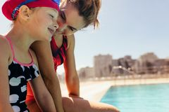 Mother and daughter at swimming pool. Mother and daughter sitting at the pool edge. Woman with girl in swimsuit at the swimming pool stock photo