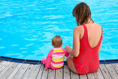 Mother and daughter sitting on the pool Stock Photo