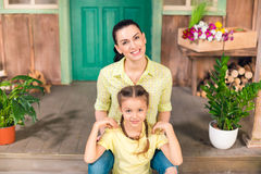 Mother and daughter sitting on porch, hugging and looking at camera Stock Photo