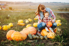 Mother and daughter sitting on pumpkins Stock Photo