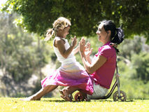 Mother and daughter (6-8) sitting on push scooter in park, girl in woman's lap, playing patter cake Royalty Free Stock Image