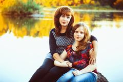 Mother and daughter sit by the river. Mother and daughter sitting on a rock by the river at sunset Royalty Free Stock Photography