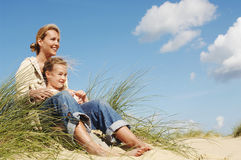 Mother And Daughter Sitting On Sand Stock Image