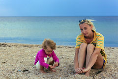Mother and daughter sitting on sand stock photo