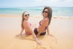 Mother and daughter sitting on a sandy beach stock photos