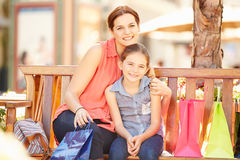 Mother And Daughter Sitting On Seat In Mall Together Stock Photos