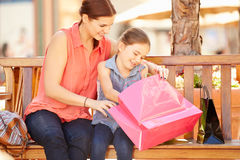 Mother And Daughter Sitting On Seat In Mall Together Stock Photography