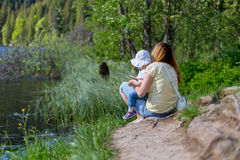 Mother and daughter sitting on the shore of a lake during summer Stock Photos