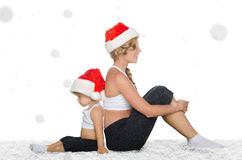 Mother and daughter sitting on snow in Santa hats Stock Photography
