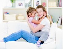 Mother with daughter sitting on the sofa Royalty Free Stock Photography