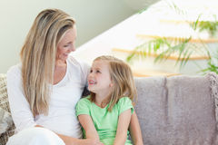 Mother and daughter sitting on sofa Stock Photography