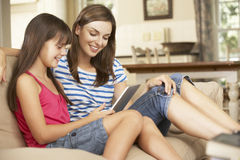 Mother And Daughter Sitting On Sofa At Home Using Tablet Computer Royalty Free Stock Images