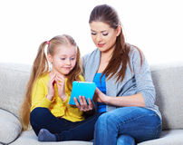 Mother with daughter sitting on sofa home work learning. Royalty Free Stock Photography