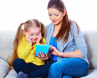Mother with daughter sitting on sofa home work learning. Stock Images