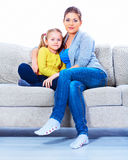 Mother and daughter sitting in sofa. Royalty Free Stock Photo