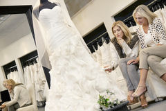 Mother and daughter sitting on sofa while looking at elegant wedding dress in bridal store Royalty Free Stock Photography
