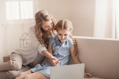 Mother and daughter sitting on sofa and using laptop at home Royalty Free Stock Photo