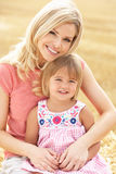 Mother And Daughter Sitting On Straw Bales In Harv Stock Photo
