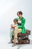 Mother and daughter sitting on suitcases Stock Photos