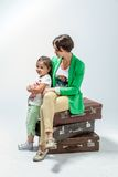 Mother and daughter sitting on suitcases Stock Images
