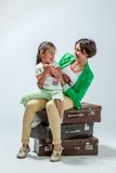 Mother and daughter sitting on suitcases Royalty Free Stock Photography