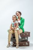 Mother and daughter sitting on suitcases Stock Photography