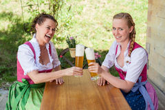 Mother and daughter sitting at a table in dirndl in front of a g stock image