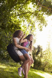 Mother And Daughter Sitting On Tire Swing In Garden Royalty Free Stock Image