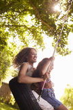 Mother And Daughter Sitting On Tire Swing In Garden Stock Photography