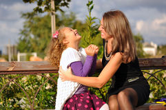 Mother and daughter. Sitting together on a bench Stock Images