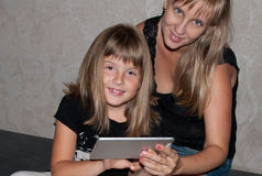 Mother and daughter. Sitting together in black with tablet Stock Photo