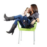 Mother and daughter sitting together on chair Royalty Free Stock Images