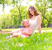 Mother and daughter sitting together on the grass Stock Images