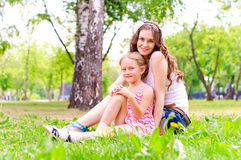 Mother and daughter sitting together on the grass Stock Photo