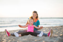 Mother and daughter sitting together stretching arms out Stock Photo