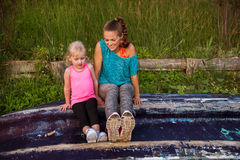 Mother and daughter sitting together on an upturned boat Stock Photography