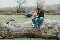 Mother and Daughter Sitting on Tree Log Stock Photo