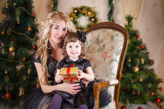 Mother and daughter sitting under Christmas tree Royalty Free Stock Images