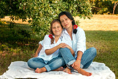 Mother and daughter sitting under an oak tree Stock Images