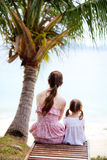 Mother and daughter sitting under palm Royalty Free Stock Images